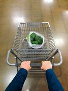 Caucasian man pushing grocery cart with broccoli Kuvituskuvat