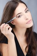 woman applying make up - stock photo