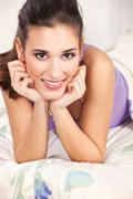 Brunette woman lying in bed Stock Photos