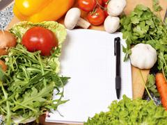 note book among the vegetables - stock photo