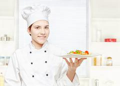 chef holding meal in kitchen - stock photo