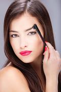 Woman combing eyebrow Stock Photos
