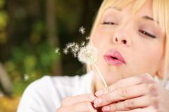 Blond woman blowing flower Stock Photos