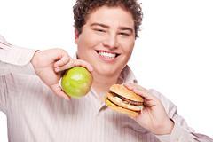 chubby man holding apple and hamburger - stock photo