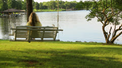 Blonde woman on swing overlooking lake Stock Footage