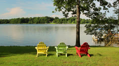 Three colorful chairs on a lake Stock Footage