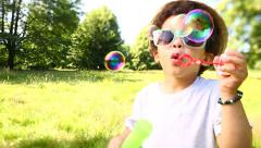 Happy boy smiling and blowing bubbles Stock Footage