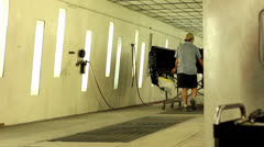 Two men push a truck bed into vehicle paint booth Stock Footage