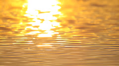 Beautiful warm sunset reflections on water surface in the lake, waves with sun - stock footage