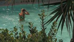 Girl Splashes Into Pool from Waterslide Stock Footage