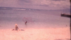 Old Vintage Film Hawaiian Man Throws Fishing Net Beach Ocean Water Sand Blue Sea - stock footage