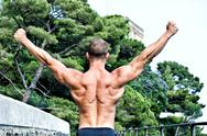 Muscular bodybuilder with hands up for victory Stock Photos