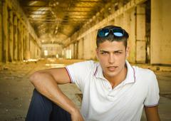 Attractive young man in abandoned, empty warehouse Stock Photos