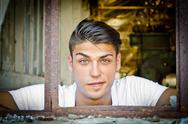 Handsome young man with funny expression in rusty window Stock Photos