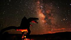 Epic milky way galaxy night timelapse passes dinosaur in silhouette to sunrise Stock Footage