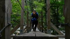 Backpacker Crossing Bridge Stock Footage