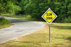 Slow Down yellow traffic sign Stock Photos