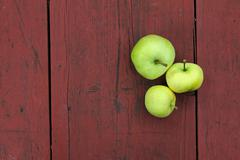 three green apples on red old wooden table - stock photo
