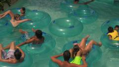 People on Lazy River Tubes Floating-by at Water Park Stock Footage