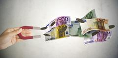 Magnet attracts many banknotes and money Stock Photos