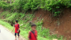 Children in jungle village coming from school Stock Footage