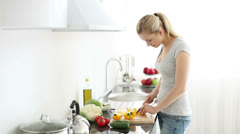 Smiling young woman in kitchen cutting bell peppers on cutting board for salad - stock footage
