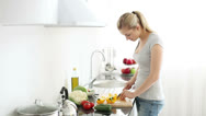 Stock Video Footage of Smiling young woman in kitchen cutting bell peppers on cutting board for salad