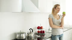 Young woman standing in kitchen eating green apple and smiling Stock Footage
