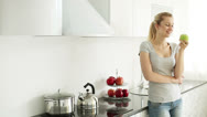 Stock Video Footage of Young woman standing in kitchen eating green apple and smiling