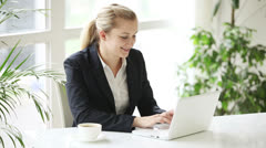 Attractive young businesswoman sitting at office table drinking coffee Stock Footage