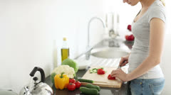 Pretty young woman slicing tomatoes on cutting board at kitchen and smiling Stock Footage