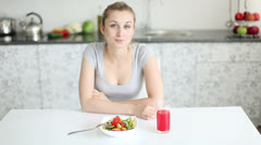 Pretty young woman sitting at table with bowl of salad in front of her  Stock Footage