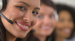 Rack focus between three customer service representatives smiling Stock Footage