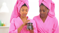 Two African American friends open spa mud and smell it Stock Footage