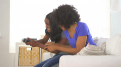 Two African American friends playing video games together - stock footage