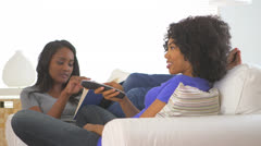 African American woman sends picture message of self while sitting with friend Stock Footage