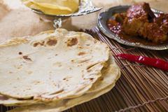 Chapatti roti, curry chicken, biryani rice, salad, masala milk tea and papado Stock Photos
