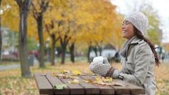 Fall woman sitting in autumn park drinking coffee - stock footage