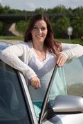 Nuori nainen nojaa autoa oven Kuvituskuvat