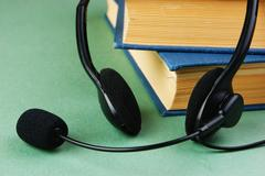 headphones with a microphone and a stack of books on a green background - stock photo