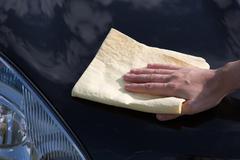 Polishing the hood of a car with a chamois Stock Photos