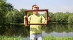 Young boy holds picture frame and imitates leaf over frames Stock Footage