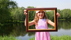 Stock Video Footage of Little girl raises picture frame and smiles near pond