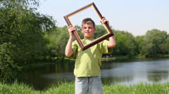 Young boy holds picture frame and rotates it near near face Stock Footage