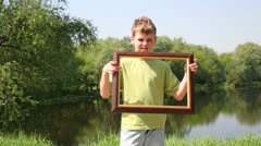 Stock Video Footage of Young boy raises picture frame and approaches close