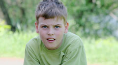 Young boy looks at background of foliage at summer day Stock Footage