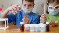 Boy and girl sit at table and make chemical experiments Stock Footage