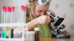Little girl attentively looks into microscope on table - stock footage
