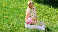 Young woman holds baby on hands while sits at lawn of dandelions Stock Footage