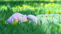 Baby girl lies and suck her finger on grass with dandelions Stock Footage